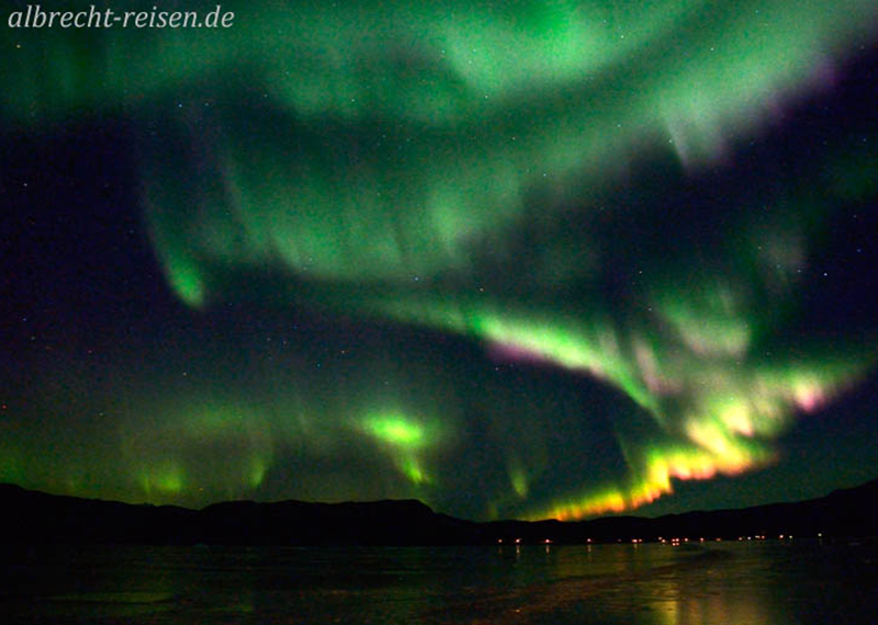 Nordlicht im Eis mit den Lichtern von Bratthlid